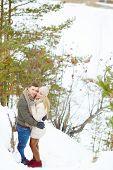 Happy boyfriend and girlfriend embracing in winter forest