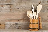 Wooden Spoons And Fork In Mug On Old Wooden Background