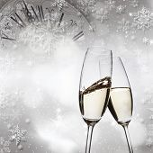 New Year's - toasting with champagne glasses against fireworks and clock close to midnight