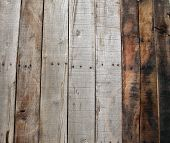 A genuine old wooden de-nailed pallet background. Wooden Pallet taken apart, the nails removed and planks laid vertical or can be turned horizontal for your use. Wood is made from trees.
