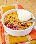Crumble cherry in bowl with ice cream on board