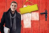 Smiling student in front of wooden door with golden plate in swiss flag colors