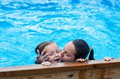 sister kissing younger sister at swimming pool