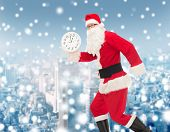christmas, holidays and people concept - man in costume of santa claus running with clock showing twelve over snowy city background