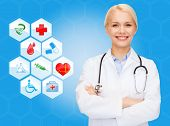 healthcare, medicine, people and symbols concept - smiling young female doctor or nurse over medical icons and blue background