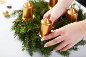 Woman Attaches Candle On A Christmas Wreath