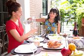 Two beautiful hispanic sisters enjoying an outdoor home meal together, one pouring water into a glass.
