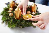 Woman Attaches Orange On Christmas Wreath