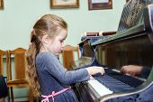 Cute Little Girl Playing Grand Piano