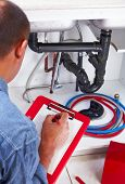 pic of plumber  - Plumber hands writing on clipboard - JPG