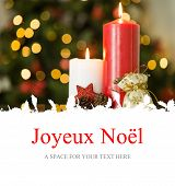 Joyeux noel against focus on christmas candles and decorations