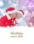 festive mature couple holding gift against gl�?�¼ckliches neues jahr