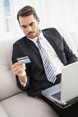 Businessman shopping online on his couch at home in the living room