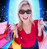 Happy blonde holding shopping bags against glittering screen on black background