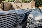 picture of urbanisation  - Building material stacked next to the imcomplete house that it is intended for - JPG