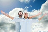 Cute couple standing with arms out against blue sky with clouds