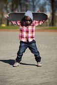 little boy with skateboard on the street