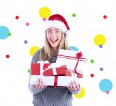 Festive blonde holding pile of gifts against dot pattern