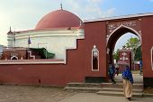 Unidentified people exit Ulugh Khan Jahan's mausoleum, Bagerhat, Bangladesh.