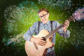 Geeky hipster playing the guitar against colourful fireworks exploding on black background