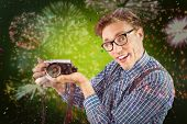 Geeky hipster holding a retro camera against colourful fireworks exploding on black background