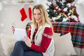 Cute blonde sitting on couch holding credit card and tablet against snowflakes
