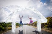 Excited couple jumping on the road against house outline in clouds