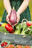 Natural New Year against hands holding an aubergine