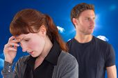 Worried woman with man behind against bright blue sky with clouds