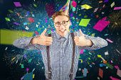 Geeky hipster wearing party hat smiling at camera against white fireworks exploding on black background