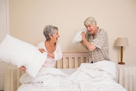 foto of pillow-fight  - Senior couple having a pillow fight at home in the bedroom - JPG