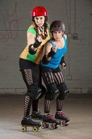 pic of roller-derby  - Female roller derby skaters in helmets pointing and shaking fists - JPG