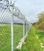 picture of barbed wire fence  - Concertina wire atop a fence protect in the nature - JPG