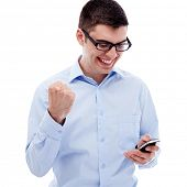 stock photo of cheers  - Portrait of cheerful young man in glasses looking at screen of smartphone and cheering isolated on white background - JPG