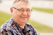 foto of cheer-up  - Close up outdoors portrait of smiling middle aged man in glasses and cheered shirt - JPG