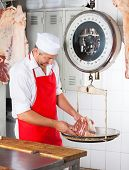image of slaughterhouse  - Male butcher weighing meat on scale at counter in butchery - JPG