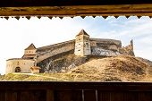 stock photo of fortified wall  - View to the Medieval fortress on the hill in Rasnov Transylvania Romania throung the fort wall - JPG