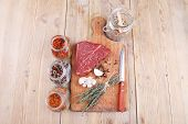 foto of peppercorns  - raw beef meat fillet with peppercorn and thyme and different spices in glass bottles ready to grill on wood figured aged board over table - JPG