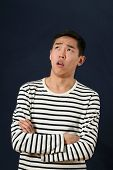 picture of disappointed  - Disappointed young Asian man with crossed hands looking up - JPG