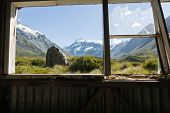 picture of hooker  - Mount Cook in the distance with Hookers Track foreground through an historic old trampers hut window - JPG