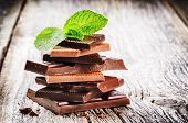 picture of wood pieces  - Stack of dark and milk chocolate pieces with mint leaf on old wood background - JPG