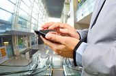 pic of escalator  - Business Man Using Mobile while going down Escalator - JPG