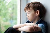 picture of sad boy  - Sad pensive child sitting on the window - JPG