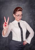 stock photo of cynicism  - Beautiful fashion woman showing victory sign on the blackboard background - JPG