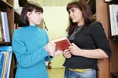 stock photo of librarian  - Woman librarian gives the female student a book - JPG