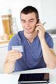 Attractive Young Man Talking On Phone Holding A Card In The Kitchen