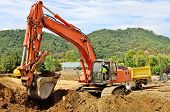 pic of excavator  - A large track hoe excavator digs dirt and rock for a new fill layer on a commercial construciton road project - JPG