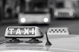 image of emblem  - automobile emblem and sign of a taxi against city streets with the vague image of buses and the included headlights in monochrome tones - JPG