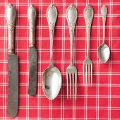 stock photo of kitchen utensils  - the old cutlery on a checkered tablecloth - JPG