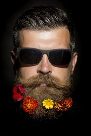 stock photo of long beard  - Head of gloomy unshaven man in sunglasses with long beard and hendlebar flowerbed moustache with marigolds flowers orange red and yellow color isolated on black background vertical picture - JPG